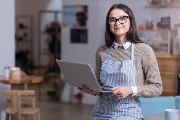 Готов к работе. красивая амбициозная женщина улыбается и держит ноутбук, стоя в кафе.
