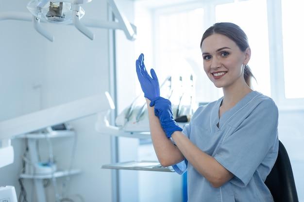 일할 준비가되었습니다. 아름 다운 젊은 여성 치과 의사 고무 장갑을 씌우고 치료를 위해 준비하는 동안 카메라에 미소
