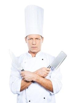 準備オーケー。彼の手でナイフを保持し、白い背景に立っている間カメラを見て白い制服を着た自信を持って成熟したシェフ