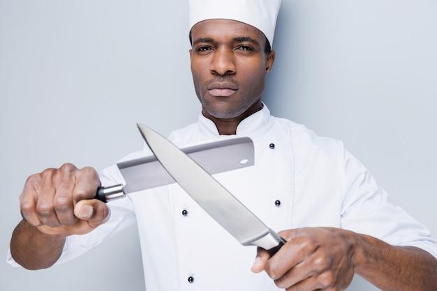 準備オーケー。彼の手にナイフを保持している白い制服を着た自信を持って若いアフリカのシェフ
