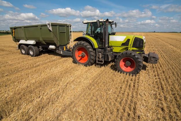 Готовый к работе зеленый трактор с прицепом-погрузчиком для нового урожая сельскохозяйственных культур.