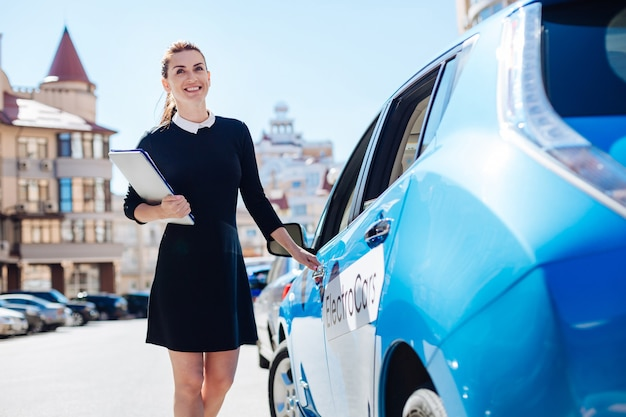 準備オーケー。彼女の車を開いている間ドキュメントを保持し、笑顔でうれしそうな前向きな幸せな実業家