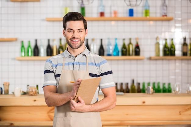 Готов к работе. профессиональный симпатичный красивый официант держит свои заметки и смотрит на вас во время работы в кафе