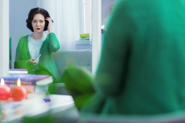 일할 준비가되었습니다. 작업을 준비하는 동안 그녀의 머리를 고정 스마트 자신감 여자