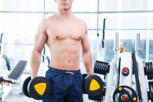ワークアウトの準備ができました。ジムに立っている間ダンベルを保持している若い筋肉の男のトリミングされた画像