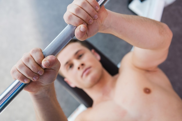 ワークアウトの準備ができました。ベンチプレスで働いている自信を持って若い筋肉の男の上面図