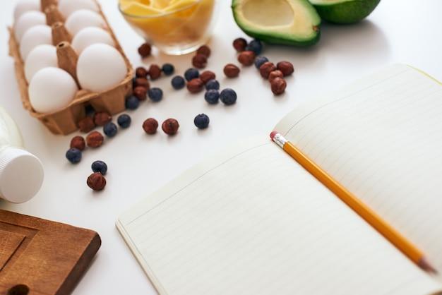 레시피를 작성할 준비가 되었습니다. 요리책, 아보카도, 계란이 말린 딸기, 치즈, 아보카도 근처 테이블에 놓여 있습니다