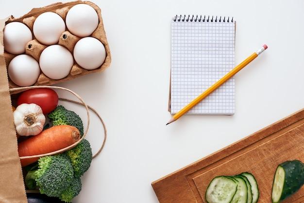 레시피를 작성할 준비가 되었습니다. 연필과 공책은 신선하고 밝은 야채와 계란 근처에 있는 탁자 위에 놓여 있습니다