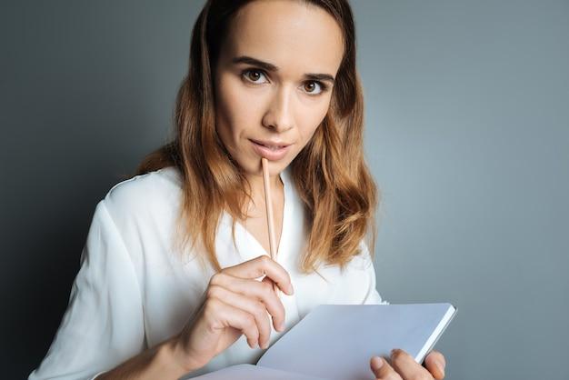 쓸 준비가되었습니다. 연필을 들고 갑작스런 영감을 받으면서 쓸 준비가 된 멋진 똑똑한 창조적 인 여자