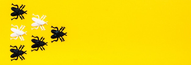 Ready web banner for halloween. white and black plastic flies on a yellow cardboard background.
