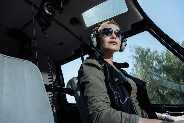 Ready to work. cheerful female helicopter pilot waiting for a passenger while being ready to start a flight
