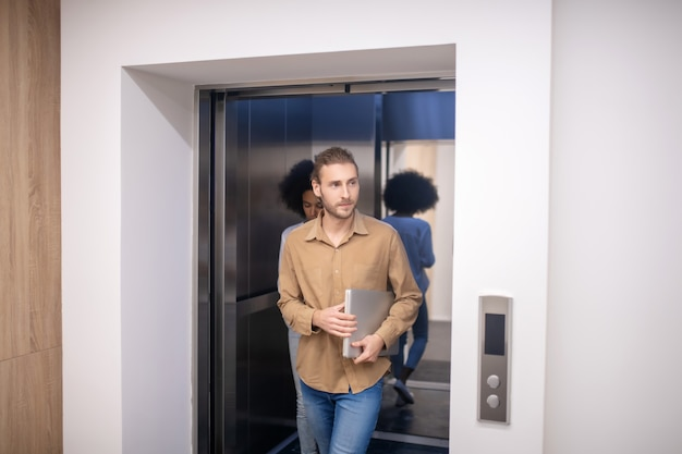 Ready to work. fair-haired bearded young man going out of the elevator