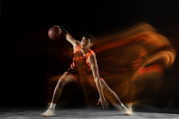 Ready. young arabian muscular basketball player in action, motion isolated on black in mixed light