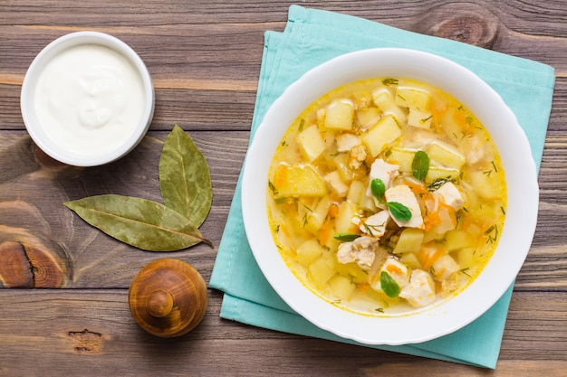 Readytoeat chicken soup with potatoes and herbs in a white bowl and sour cream on woodtable