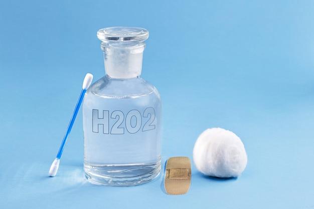 Флакон с реагентом со стеклянной пробкой, внутри находится перекись водорода. химический элемент h2 o2 в лаборатории