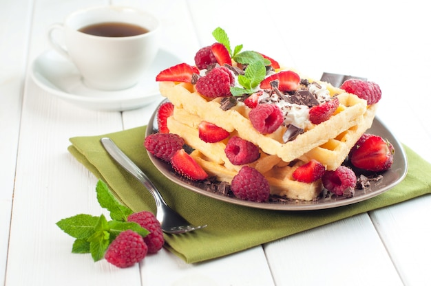 Reakfast with belgian waffles covered with raspberry and strawberry and cup of coffee