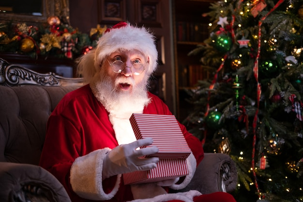 Real authentic surprised santa claus holds christmas gift. fulfillment of desires. santa sitting at