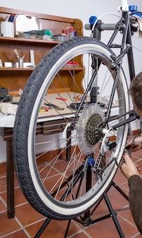 ワークショップで黒のカスタムピストバイクを修理する本物の自転車整備士