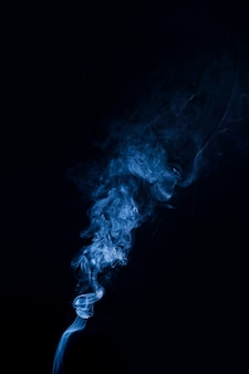 Real blue smoke billowing up on black background