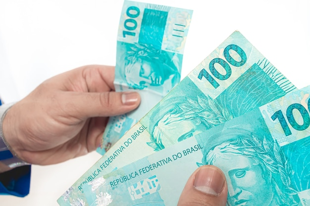 Real brazilian currency a businessman holding brazilian real money bills from brazil