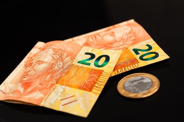 실제 brl 브라질 화폐 지폐와 사진 속 실제 동전 1개는 검정색 배경에 가깝습니다.