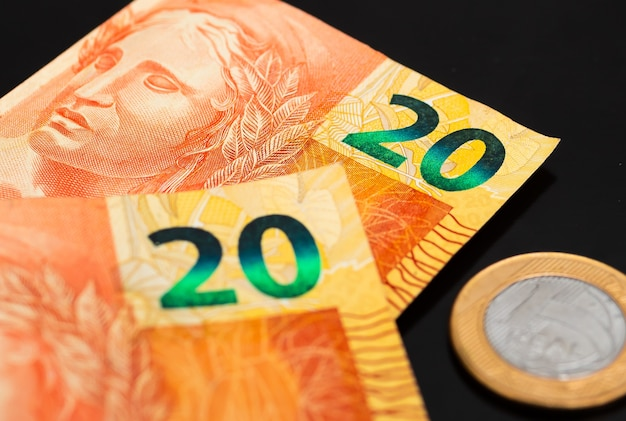 Real brl brazil money banknotes and one real coin in photography close up with black background