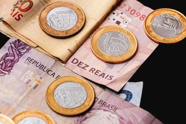 暗い机の上の本物のブラジルの紙幣と硬貨