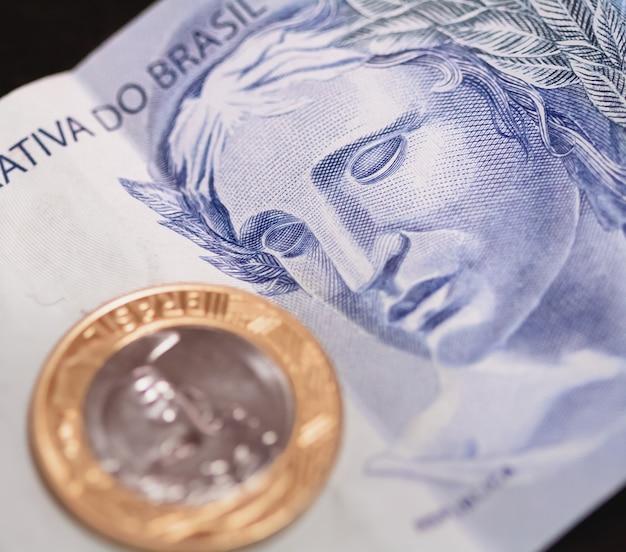 ブラジルの紙幣と1枚の本物の硬貨をクローズアップで本物のbrl