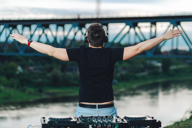 Real dj plays music at a party, stands with his back, pushing his arms out to the sides in the open air