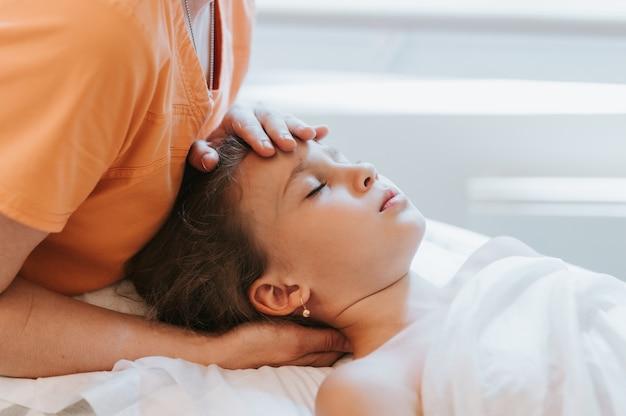 本物の医師の整骨療法の手は、8歳の子供の女の子のために生理学的および感情的な治療を行います。小児オステオパシー治療セッション。代替医療。子供の健康の世話をする
