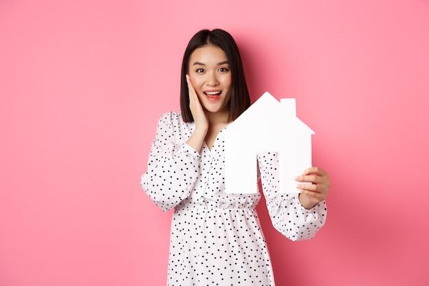 Недвижимость. взрослая азиатская женщина ищет дом, держит модель дома и улыбается, промо брокерской компании, стоящая над розовым