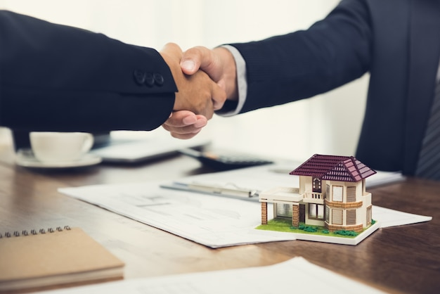Real estate agent or architect making handshake with client in the meeting