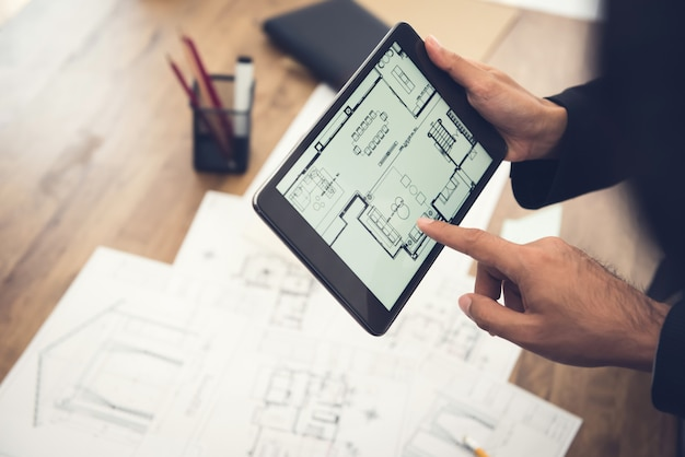 Real estate agent or architect presenting house floor plan to client on tablet computer