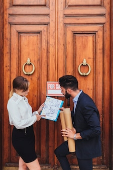 Real estate agent and architect with wooden door