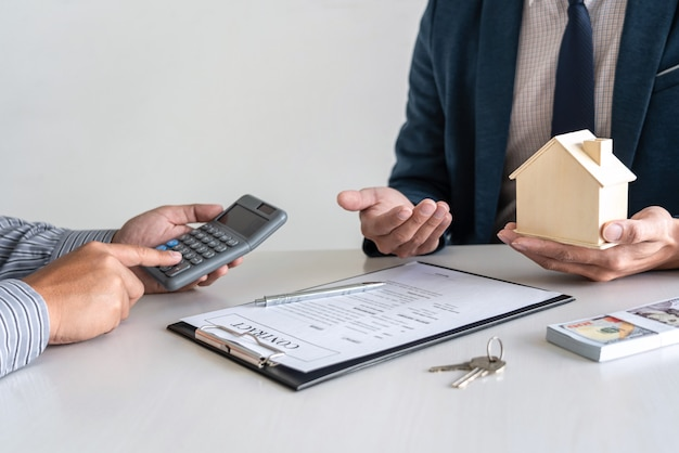 Real estate agent are presenting home loan and giving house to customer after signing contract to buy house with approved property application form.