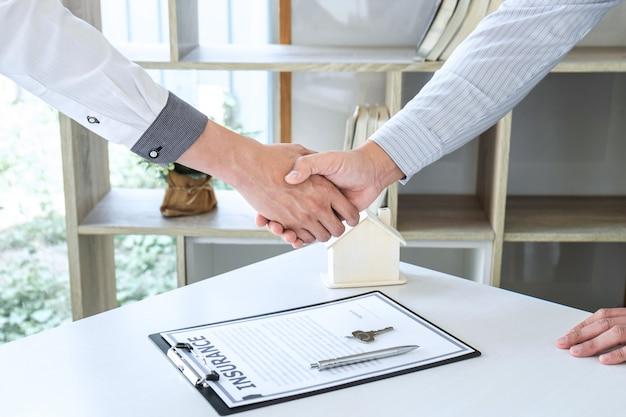 不動産業者は十分な取引の後に握手をし、顧客に家の鍵を提供しています