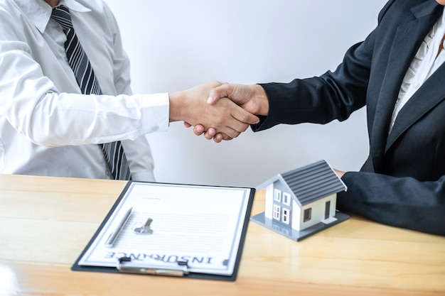 Real estate agent are shaking hands after good deal and giving house, keys to customer after discussing and signing contract to buy house with approved application form