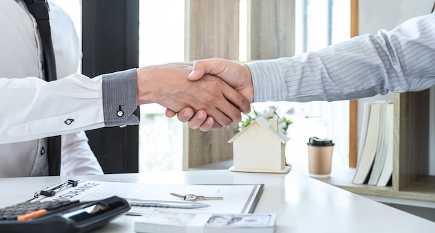 Real estate agent are shaking hands after good deal and giving house, keys to customer after signing contract