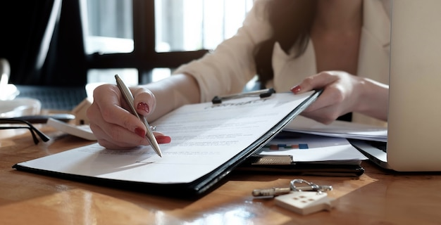 Real estate agent assisting client to sign contract paper at desk with house model