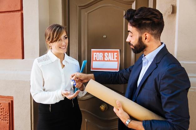Agente immobiliare e donna d'affari davanti alla porta