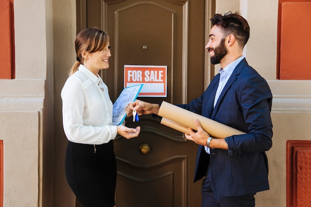 Real estate agent and business woman interchanging keys