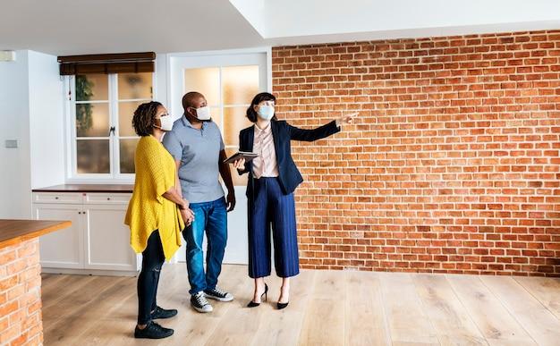 Agente immobiliare e cliente in maschera per il viso guardando un nuovo progetto