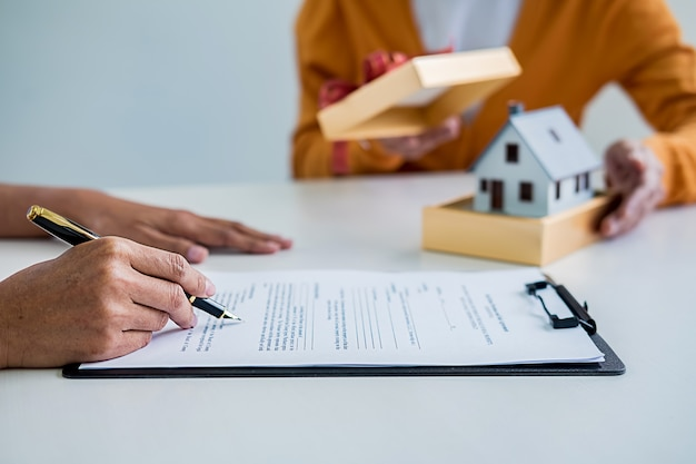Real estate agent and customer signing contract to buy house, insurance or loan real estate.