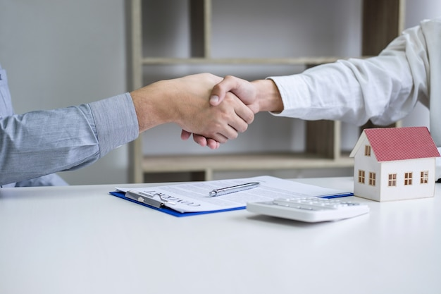 Real estate agent and customers shaking hands together celebrating finished contract after signing