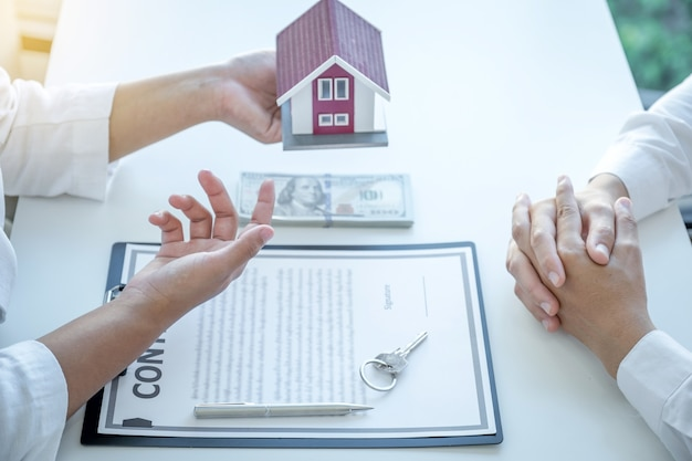 The real estate agent explains the business contract, rent, purchase, mortgage, a loan, or home insurance to the women buyer.