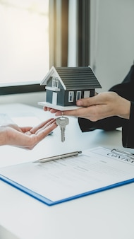A real estate agent gives a home model to the buyer woman.