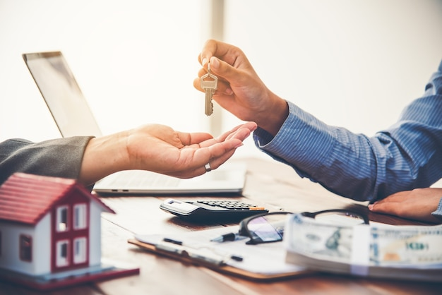 Real estate agent gives the keys to the house buyer and signs the contract in the office.