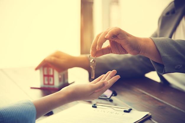 부동산 중개인은 주택 구매자에게 열쇠를주고 사무실에서 계약에 서명합니다.