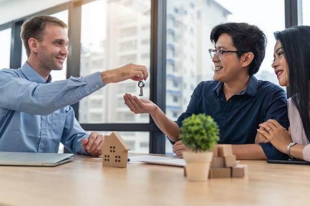 新しい家からオフィスの若いカップルにキーを与える不動産業者