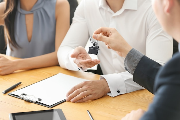 Real estate agent giving key from new house to young couple in office